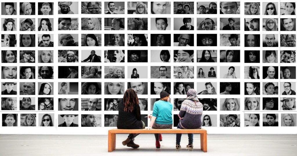 Menschen auf der Bank vor Fotowand